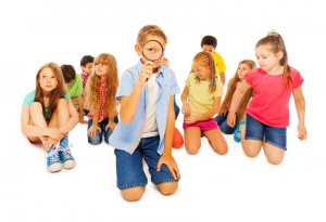 Group of friends diverse school children sit together around boy with magnifying glass